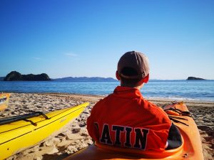 Latin School of Chicago student in kayak on a Coromandel beach